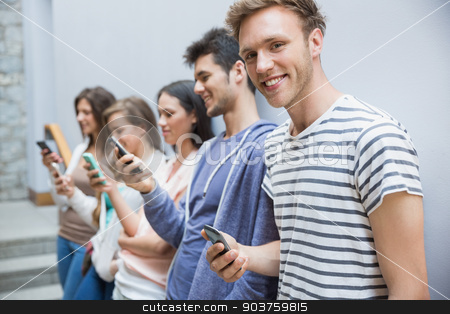 Students using their smartphones in a row stock photo, Students using their smartphones in a row at the university by Wavebreak Media