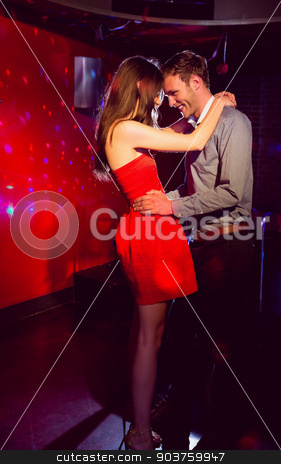 Cute couple slow dancing together stock photo, Cute couple slow dancing together at the nightclub  by Wavebreak Media