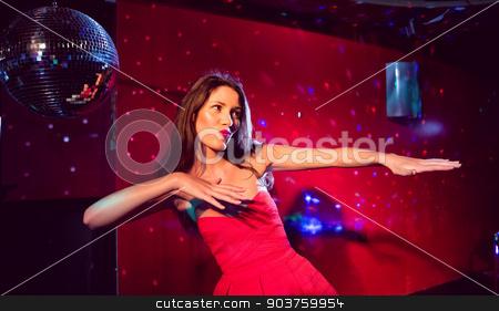 Pretty brunette dancing and smiling stock photo, Pretty brunette dancing and smiling at the nightclub  by Wavebreak Media
