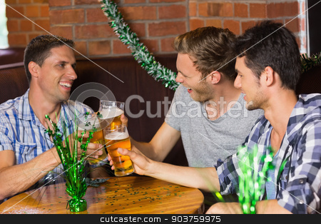 Happy friends toasting with pints of beer on patricks day stock photo, Happy friends toasting with pints of beer on patricks day in a bar by Wavebreak Media