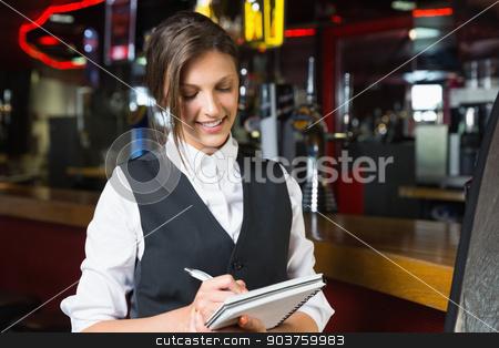 Happy barmaid writing in notepad stock photo, Happy barmaid writing in notepad in a bar by Wavebreak Media
