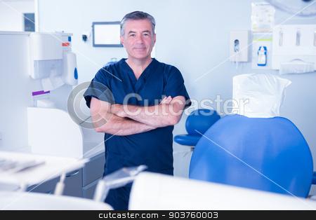 Dentist in blue scrubs smiling at camera stock photo, Dentist in blue scrubs smiling at camera at the dental clinic by Wavebreak Media