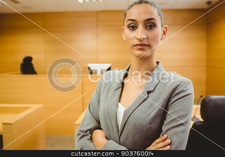 Unsmiling lawyer looking at camera crossed arms  stock photo, Unsmiling lawyer looking at camera crossed arms in the court room by Wavebreak Media