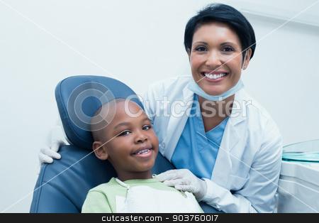 Portrait of female dentist examining boys teeth stock photo, Portrait of female dentist examining boys teeth in the dentists chair by Wavebreak Media