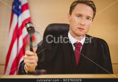 Serious judge about to bang gavel on sounding block stock photo, Serious judge about to bang gavel on sounding block in the court room by Wavebreak Media