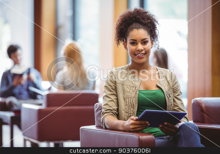 Student sitting on sofa using her tablet pc smiling at camera stock photo, Student sitting on sofa using her tablet pc smiling at camera at the university by Wavebreak Media