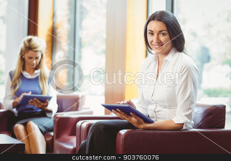 Smiling business colleagues with digital tablet stock photo, Smiling business colleagues with digital tablet in the office by Wavebreak Media