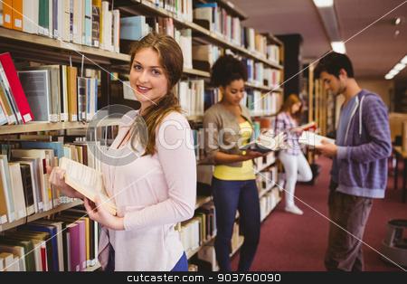 Happy student taking book from shelf stock photo, Happy student taking book from shelf in library by Wavebreak Media