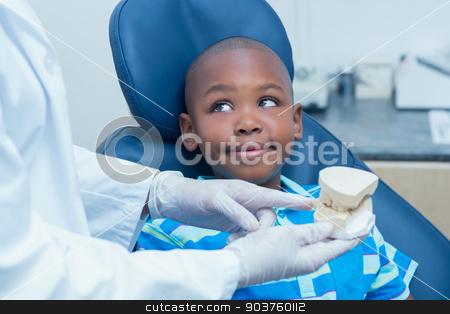 Cropped dentist showing boy prosthesis teeth stock photo, Cropped dentist showing young boy prosthesis teeth in the dentists chair by Wavebreak Media