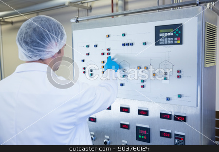 Scientist using the machine and pressing on buttons stock photo, Scientist using the machine and pressing on buttons in the factory by Wavebreak Media