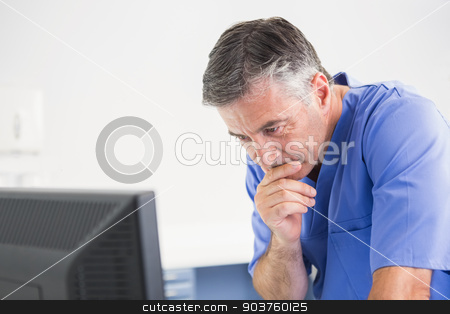 Thoughtful dentist using computer  stock photo, Thoughtful dentist using computer in dental clinic by Wavebreak Media
