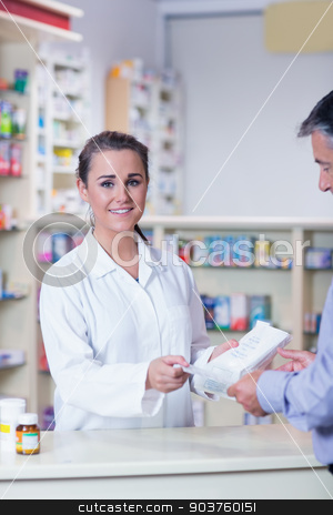 Portrait of a smiling pharmacist holding a prescription stock photo, Portrait of a smiling pharmacist holding a prescription in the pharmacy by Wavebreak Media