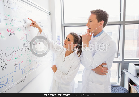 Science student and lecturer looking at whiteboard stock photo, Science student and lecturer looking at whiteboard at the laboratory by Wavebreak Media