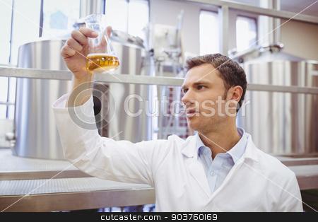 Focused scientist examining beaker with beer stock photo, Focused scientist examining beaker with beer in the factory by Wavebreak Media