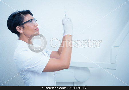 Female dentist in surgical mask holding injection stock photo, Side view of female dentist holding injection by Wavebreak Media