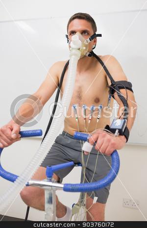 Man doing fitness test on exercise bike stock photo, Man doing fitness test on exercise bike at the medical centre by Wavebreak Media