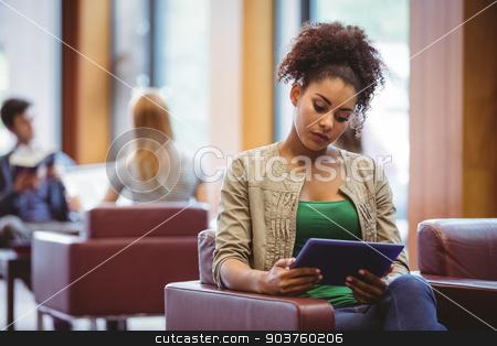 Focused student sitting on sofa using her tablet pc stock photo, Focused student sitting on sofa using her tablet pc at the univeristy by Wavebreak Media