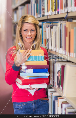 Mature student in library holding books stock photo, Mature student in library holding books at the university by Wavebreak Media