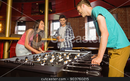Smiling friends student playing table football in competition stock photo, Smiling friends student playing table football in competition in a pub by Wavebreak Media