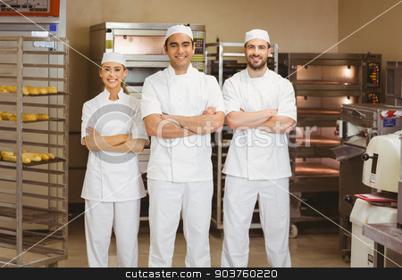 Team of bakers smiling at camera stock photo, Team of bakers smiling at camera in a commercial kitchen by Wavebreak Media