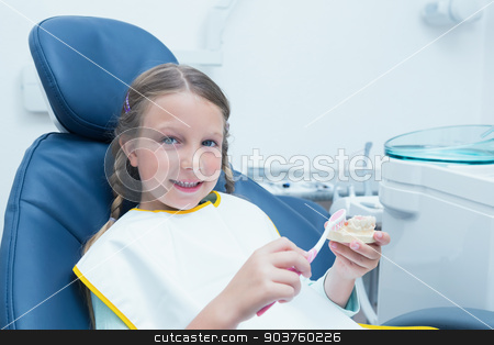 Little girl learning how to brush teeth stock photo, Little girl learning how to brush teeth in the dentists chair by Wavebreak Media