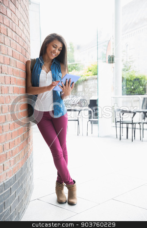 Pretty student smiling and holding tablet stock photo, Pretty student smiling and holding tablet at the university by Wavebreak Media
