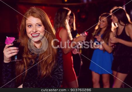 Pretty redhead drinking a cocktail stock photo, Pretty redhead drinking a cocktail at the nightclub  by Wavebreak Media