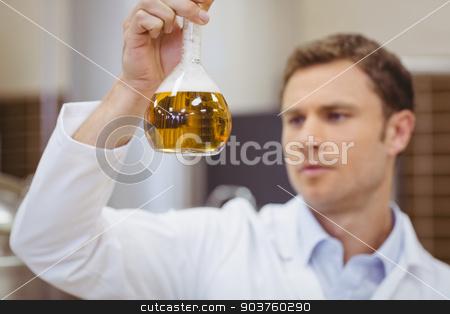 Focused scientist holding beaker with beer stock photo, Focused scientist holding beaker with beer in the factory by Wavebreak Media