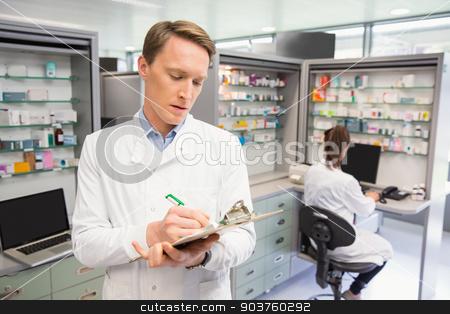 Focused pharmacist writing on clipboard stock photo, Focused pharmacist writing on clipboard at the hospital pharmacy by Wavebreak Media
