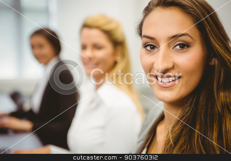 Happy women in computer room smiling at camera stock photo, Happy women in computer room smiling at camera in the office by Wavebreak Media