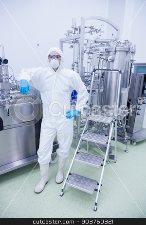 Scientist in protective suit leaning against machine stock photo, Scientist in protective suit leaning against machine in the factory by Wavebreak Media