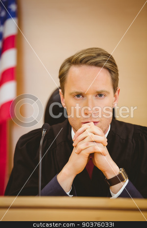 Unsmiling judge with american flag behind him stock photo, Unsmiling judge with american flag behind him in the court room by Wavebreak Media