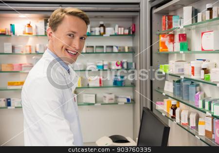 Handsome pharmacist using the computer stock photo, Handsome pharmacist using the computer at the hospital pharmacy by Wavebreak Media