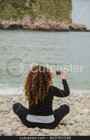 Young woman, finds herself alone, taking advantage of the holida stock photo, Mature Woman on vacation, go to the beach to find herself, and use smartphone, solitude. by GCammarata