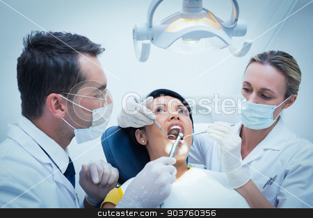 Male dentist with assistant examining womans teeth stock photo, Male dentist with assistant examining womans teeth in the dentists chair by Wavebreak Media