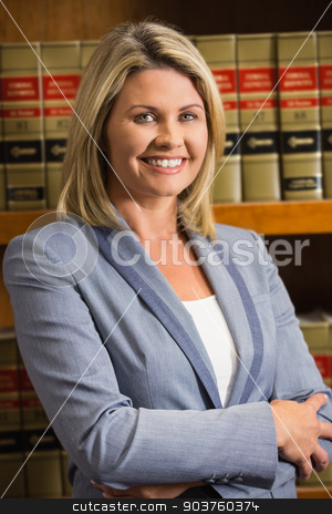 Lawyer smiling at camera in law library stock photo, Lawyer smiling at camera in law library at the university by Wavebreak Media