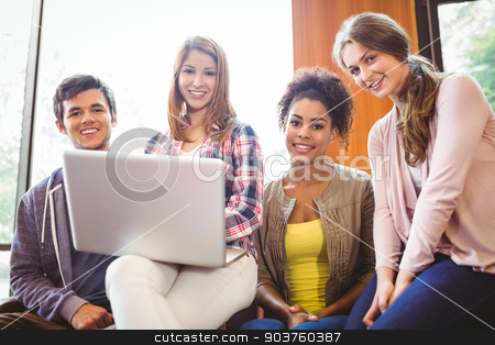 Smiling students sitting on couch using laptop stock photo, Smiling students sitting on couch using laptop at the university by Wavebreak Media