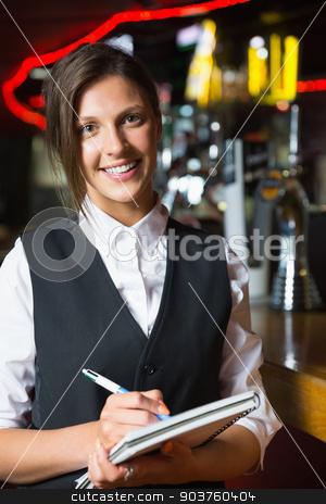 Happy barmaid smiling at camera taking notes stock photo, Happy barmaid smiling at camera taking notes in a bar by Wavebreak Media