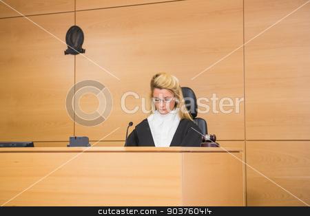 Stern judge sitting and listening stock photo, Stern judge sitting and listening in the court room by Wavebreak Media