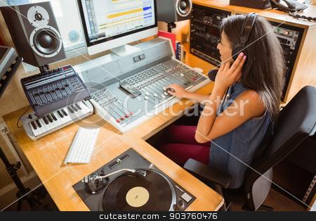 Smiling university student mixing audio  stock photo, Smiling university student mixing audio in the studio of a radio by Wavebreak Media