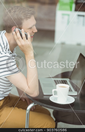 Smiling student using laptop and smartphone in cafe  stock photo, Smiling student using laptop and smartphone in cafe at the university by Wavebreak Media