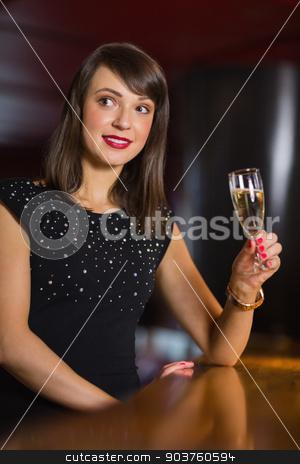 Pretty brunette drinking glass of champagne stock photo, Pretty brunette drinking glass of champagne in a bar by Wavebreak Media