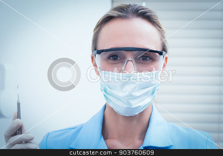 Female dentist in surgical mask holding injection stock photo, Portrait of female dentist in surgical mask and safety glasses holding injection by Wavebreak Media