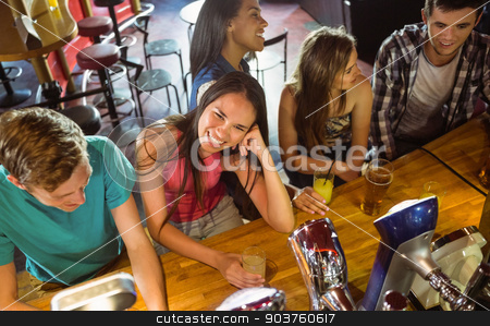 Smiling friends talking and drinking beer and mixed drink stock photo, Smiling friends talking and drinking beer and mixed drink in a bar by Wavebreak Media