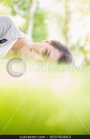 Pretty brunette lying on the grass stock photo, Pretty brunette lying on the grass on a sunny day by Wavebreak Media