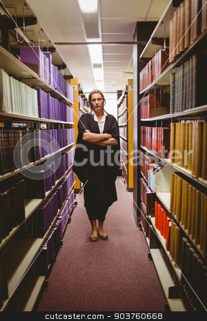 Stern lawyer standing between shelfs with arms crossed stock photo, Stern lawyer standing between shelfs with arms crossed in library by Wavebreak Media