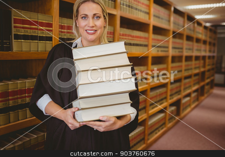 Smiling lawyer holding heavy pile of books standing stock photo, Smiling lawyer holding heavy pile of books standing in library by Wavebreak Media