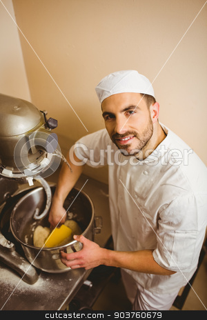 Baker using large mixer to mix dough stock photo, Baker using large mixer to mix dough in a commercial kitchen by Wavebreak Media