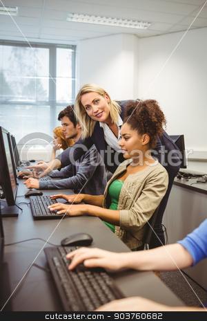 Happy computer teacher smiling at camera during her class stock photo, Happy computer teacher smiling at camera during her class at the university by Wavebreak Media