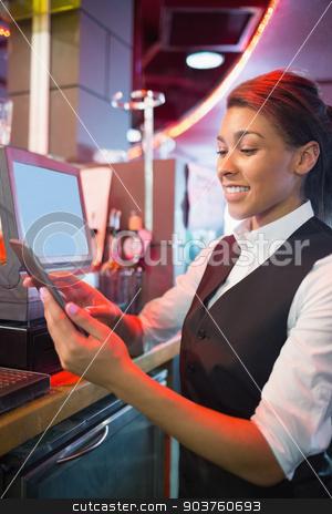 Pretty barmaid using touchscreen till  stock photo, Pretty barmaid using touchscreen till in a bar by Wavebreak Media